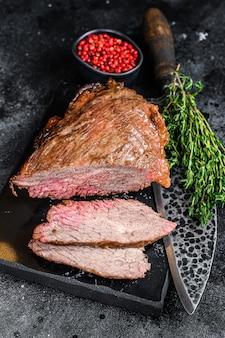 Rosbief tri tip steak bbq. zwarte achtergrond. bovenaanzicht.
