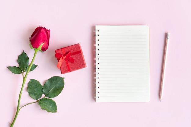 Rose, geschenkdoos en notitieboekje op roze achtergrond. valentijnsdag, jubileum, verjaardag concept. plat leggen, bovenaanzicht, kopie ruimte.