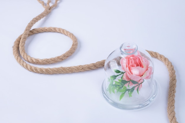 Rose in glazen beker met touw op wit oppervlak.