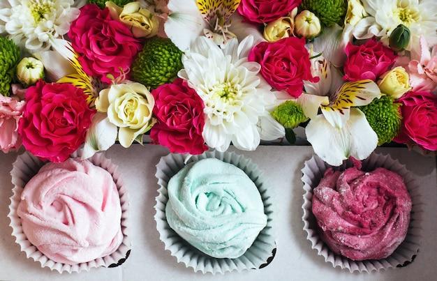Rose marshmallows en prachtige bloemen op wit