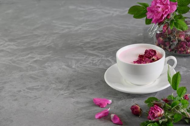 Rose moon melk in glazen op grijze achtergrond. vooraanzicht. detailopname.