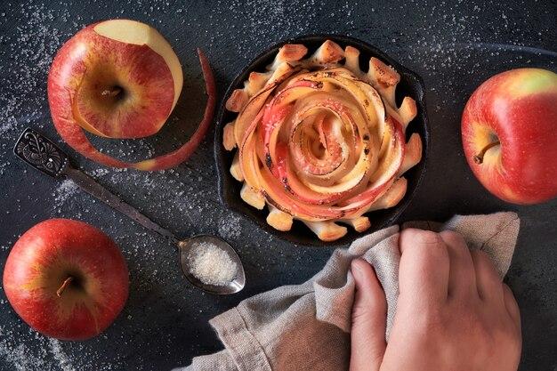 Rose shaped appelgebak in ijzer koekepan op donker met sommige appels en suiker