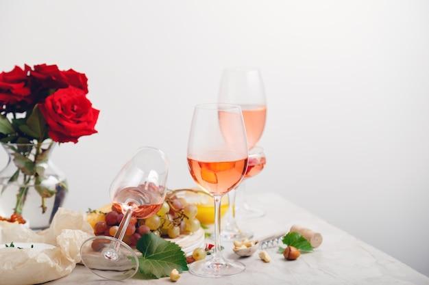 Rose wijn en zomer drinkt roze cocktails met druiven op de feestelijke tafel versierd met bloemen op feest evenement. groepsglazen roze wijn minimale lay-out met exemplaarruimte.
