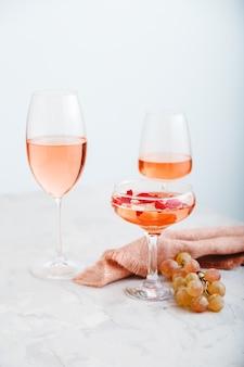 Rose wijn in verschillende soorten glazen op lichte betonnen ondergrond met druiven. wijnsamenstelling op witte tafel. verticale foto.