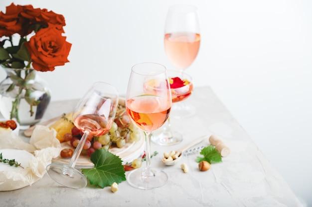 Rose wijn in verschillende wijnglazen fles op witte tafel met druiven kaas, snacks boeket bloemen. moderne stilleven rose wine samenstelling op lichtgrijze betonnen achtergrond.