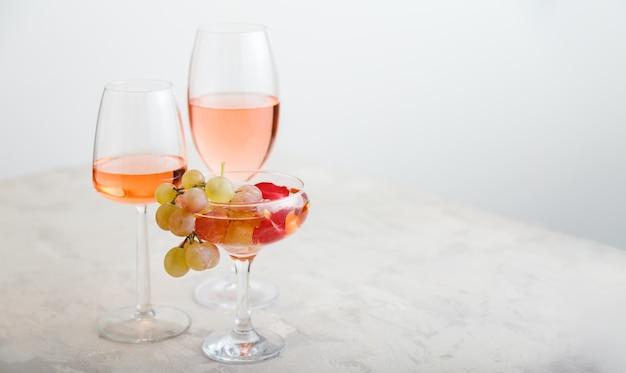 Rose wijn in verschillende wijnglazen op witte tafel met roze druiven moderne stilleven wijn