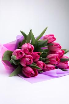 Rosebuds van roze tulpen liggen op een witte tafel. een boeket lentebloemen voor een vakantie