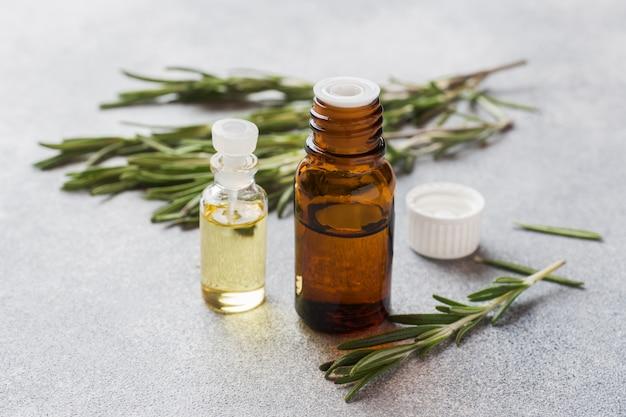 Rosemary etherische olie in een glazen fles met verse tak rozemarijn kruid
