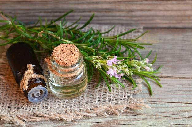 Rosemary etherische olie in glazen flessen met vers groen rozemarijnkruid op oud hout