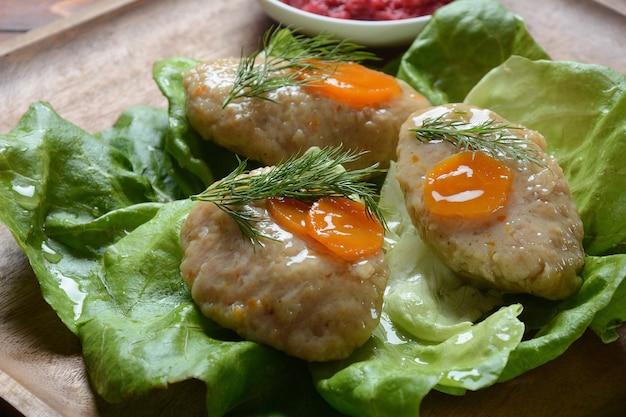 Rosh hashana-tafelsetting. traditionele joodse pascha-gefilte vis met wortelen, sla en mierikswortel.