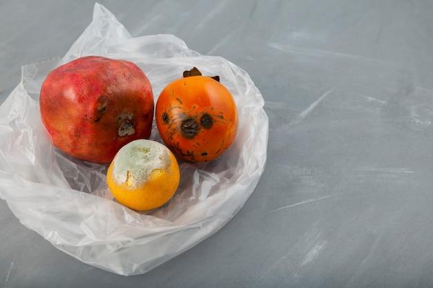 Rot fruit granaatappel, persimmon, sinaasappel in biologisch afbreekbare plastic zak op grijs