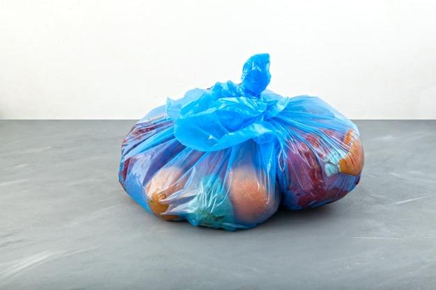 Rot fruit in blauwe vuilniszak biologisch voedselafval onvolmaakte bewaargroenten en fruit