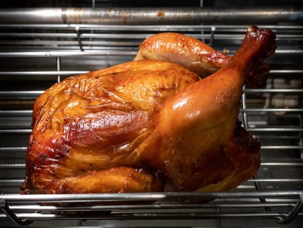 Roterende machine zijn gegrilde hele kip. geroosterde kippen in een rij die bij industriële brander draaien. een barbecue gebraden spies in een commerciële oven rotisserie.