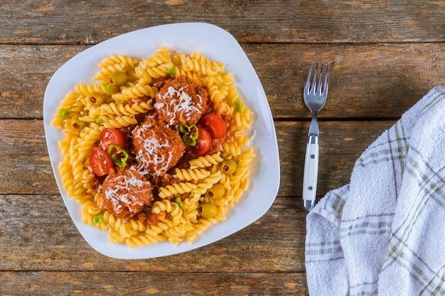 Rotini-pasta met gehaktballetjes in tomatensaus en olijven in kom.