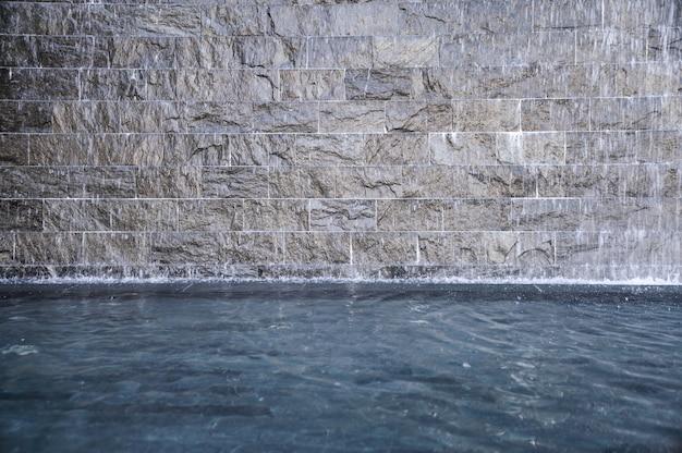 Rots grijze fontein die in vijver stroomt