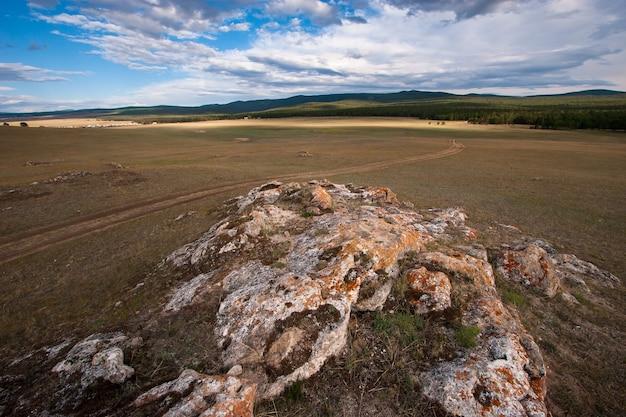 Rots in de steppe in de buurt van de weg naar het bos. op de rots is rood mos. steppe met geel en groen gras. wolken in de lucht.