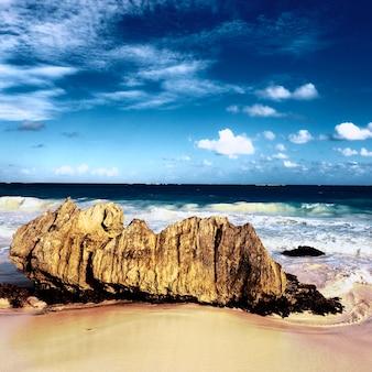 Rots in het strand met dramatische hemel op vierkant formaat