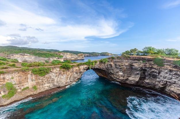 Rots kustlijn. stenen boog over de zee. gebroken strand, nusa penida, indonesië