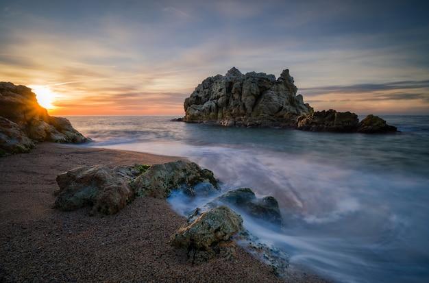 Rotsachtig eiland in de buurt van het strand van een prachtige zee bij zonsondergang