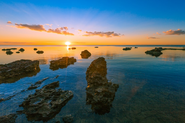 Rotsachtig strand bij zonsondergang