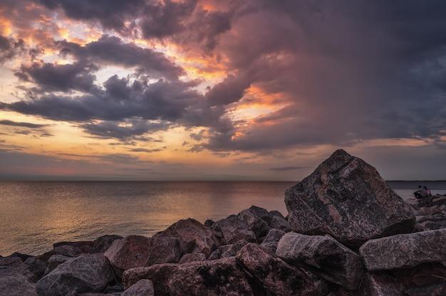 Rotsachtig strand met zonsondergangachtergrond.