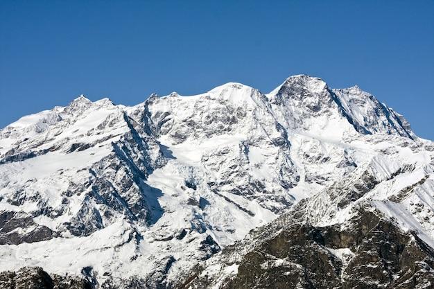 Rotsachtige berg bedekt met de zee onder het zonlicht en een blauwe lucht overdag