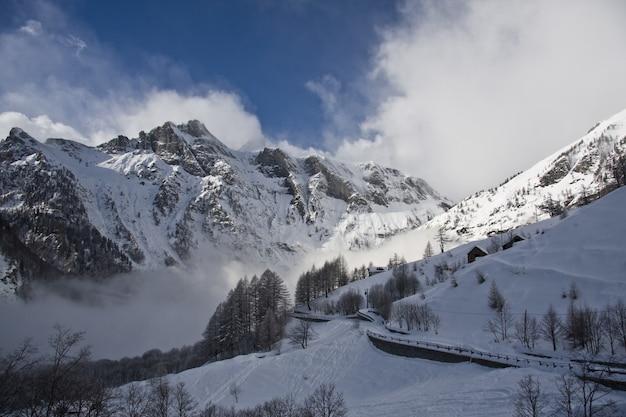Rotsachtige berg bedekt met sneeuw en mist tijdens de winter met een blauwe lucht in de
