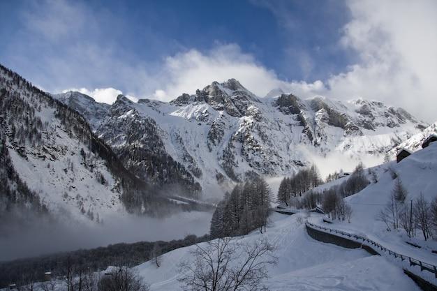 Rotsachtige berg bedekt met sneeuw en mist tijdens de winter met een blauwe lucht