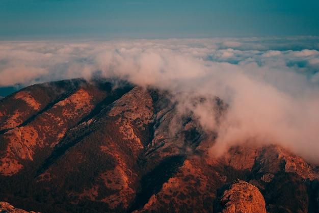 Rotsachtige berg bij mistig weer in de schemering