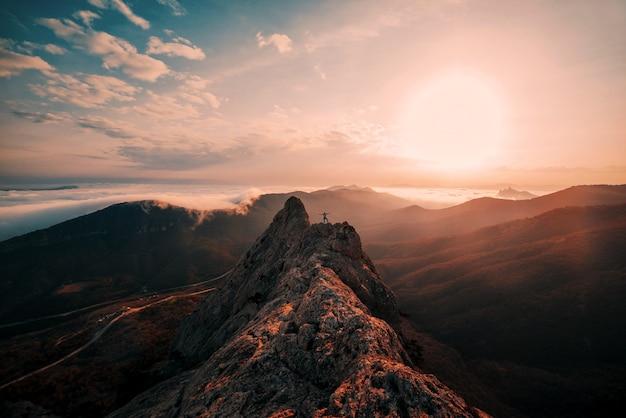 Rotsachtige berg in mistig bij zonsondergang