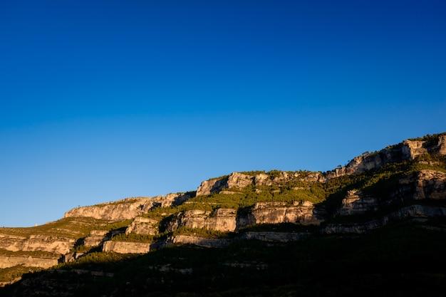 Rotsachtige bergen bij zonsondergang, met een schone blauwe hemel en exemplaarruimte.