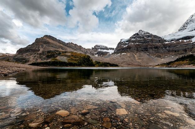 Rotsachtige bergen met bewolkt in blauwe hemelbezinning over lake magog