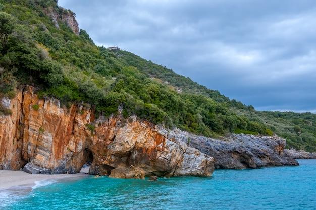 Rotsachtige boskust van de zee bij bewolkt weer. villa op de helling. op het strand staat een natuurstenen boog