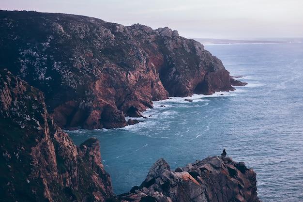 Rotsachtige heuvels en oceaan, eenzame man kijkt naar de prachtige natuur