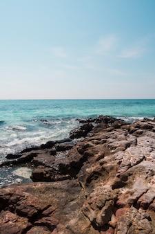 Rotsachtige idyllische zee tegen de blauwe hemel
