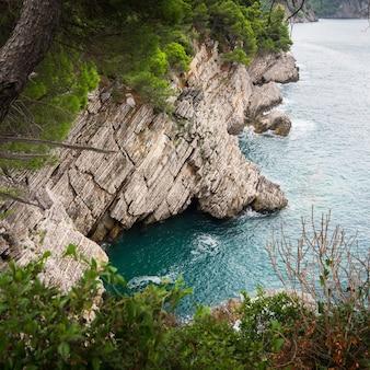 Rotsachtige klif boven de turquoise zee en dennen