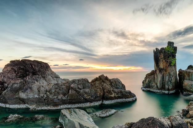 Rotsachtige klif strekt zich uit tot in de zee met de hemel na zonsondergang. kaap chai chet .trat thailand