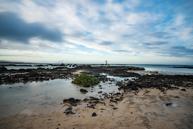 Rotsachtige kust van noordelijk lanzarote bij eb op een bewolkte dag