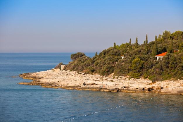 Rotsachtige kustlijn en klein dorp dichtbij pula, kroatië