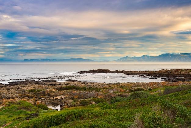 Rotsachtige kustlijn op de oceaan in de kelders, zuid-afrika, beroemd om walvissen te spotten. wintertijd, bewolkte en dramatische hemel.