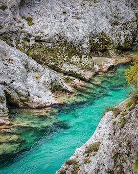 Rotsachtige oevers van de smaragdgroene rivier soca in de herfst seizoen in slovenië