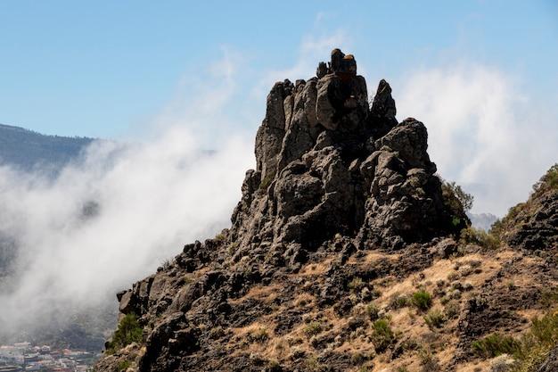 Rotsachtige piek omringd door wolken