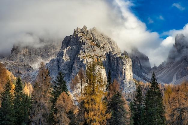Rotsachtige pieken van dolomieten en kleurrijke bomen in de herfst seizoen, italië