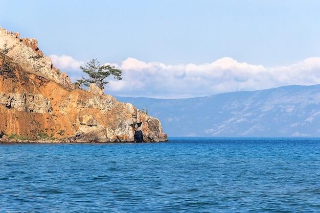 Rotsachtige steile rots en boom op het meer baikal in de zomer