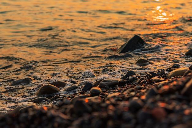 Rotsachtige zee strand bij zonsondergang prachtige kleuren op de rotsen