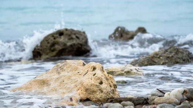 Rotsen aan de zeekust, schuim en golven
