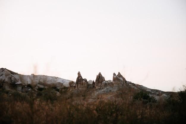 Rotsen die als paddestoelen kijken die dramatisch door een zonsondergang in cappadocia, turkije worden aangestoken