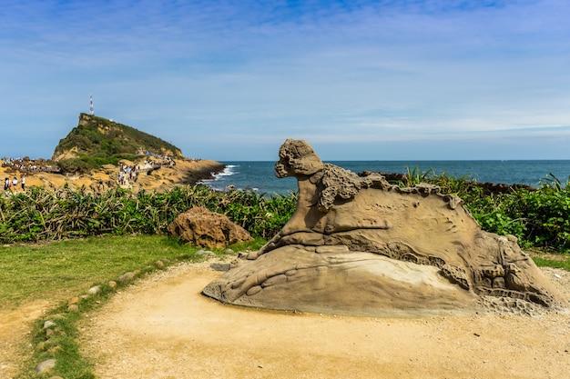 Rotsen die worden uitgehold door de natuur bij yehliu geopark en de kust van yehliu in wazige achtergrond met blauwe bewolkte hemel en zee