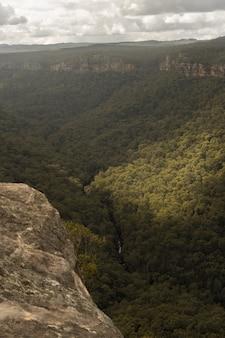 Rotsen en bergen bedekt met bossen onder een bewolkte hemel en zonlicht