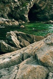 Rotsen en grot aan de kust, bewolkt weer op zee, kustlijn van telyakovsky bay primorsky krai, rusland.